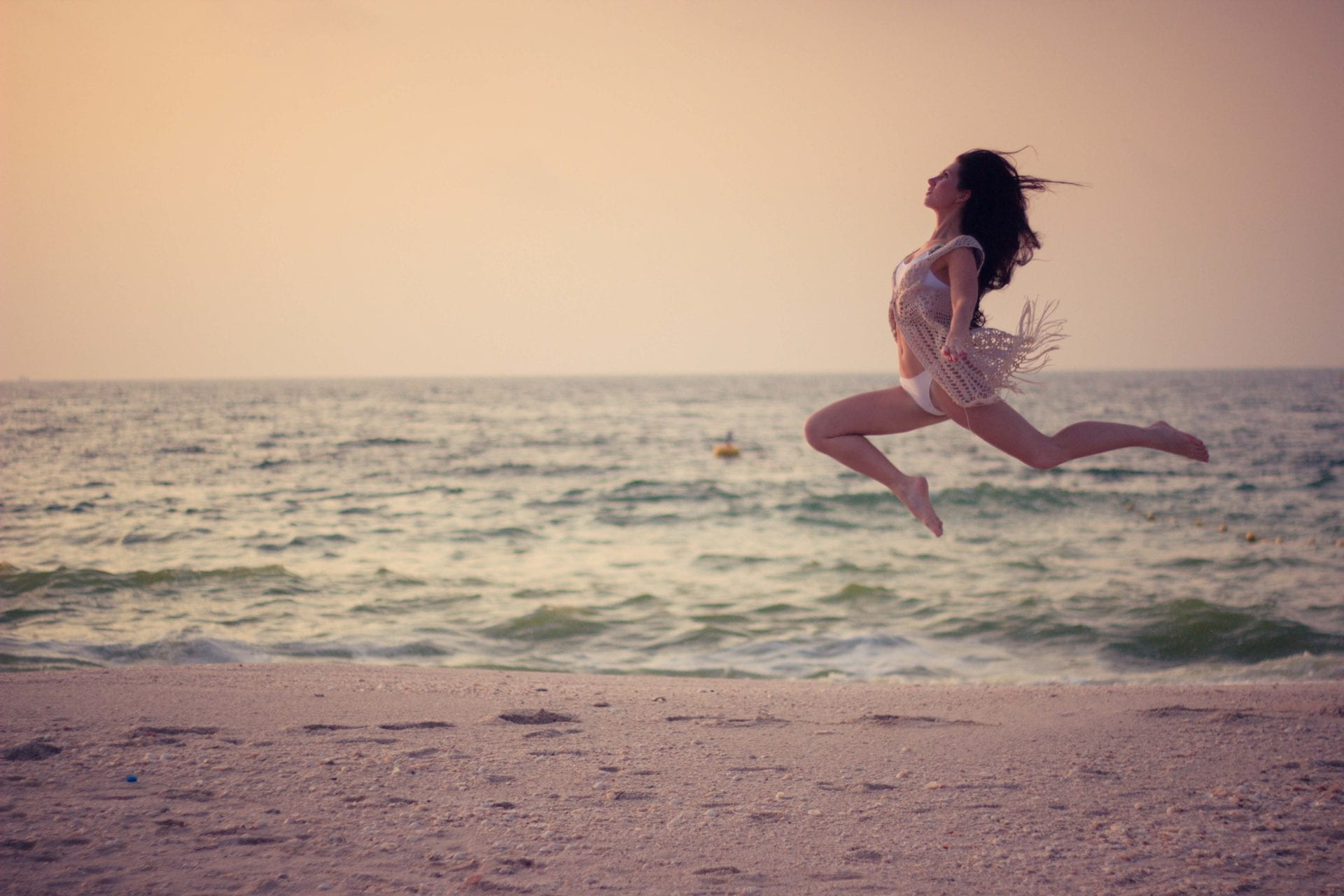 Jogínka s dlouhými vlasy ve skoku na pláži v Dubaji, jóga Liberec a Turnov, ceník jogy v Libereci a Turnově