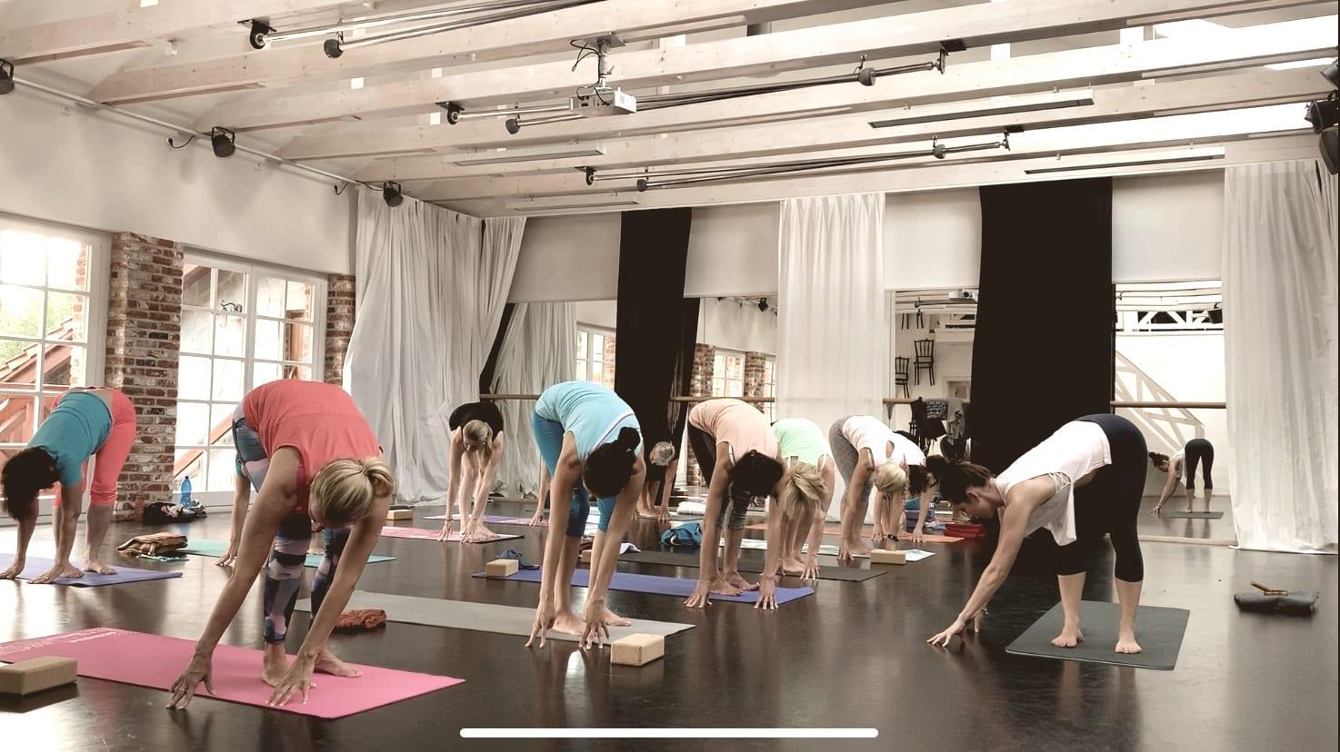 jogínky a jogíni v pozici hlubokého předklonu v protažení