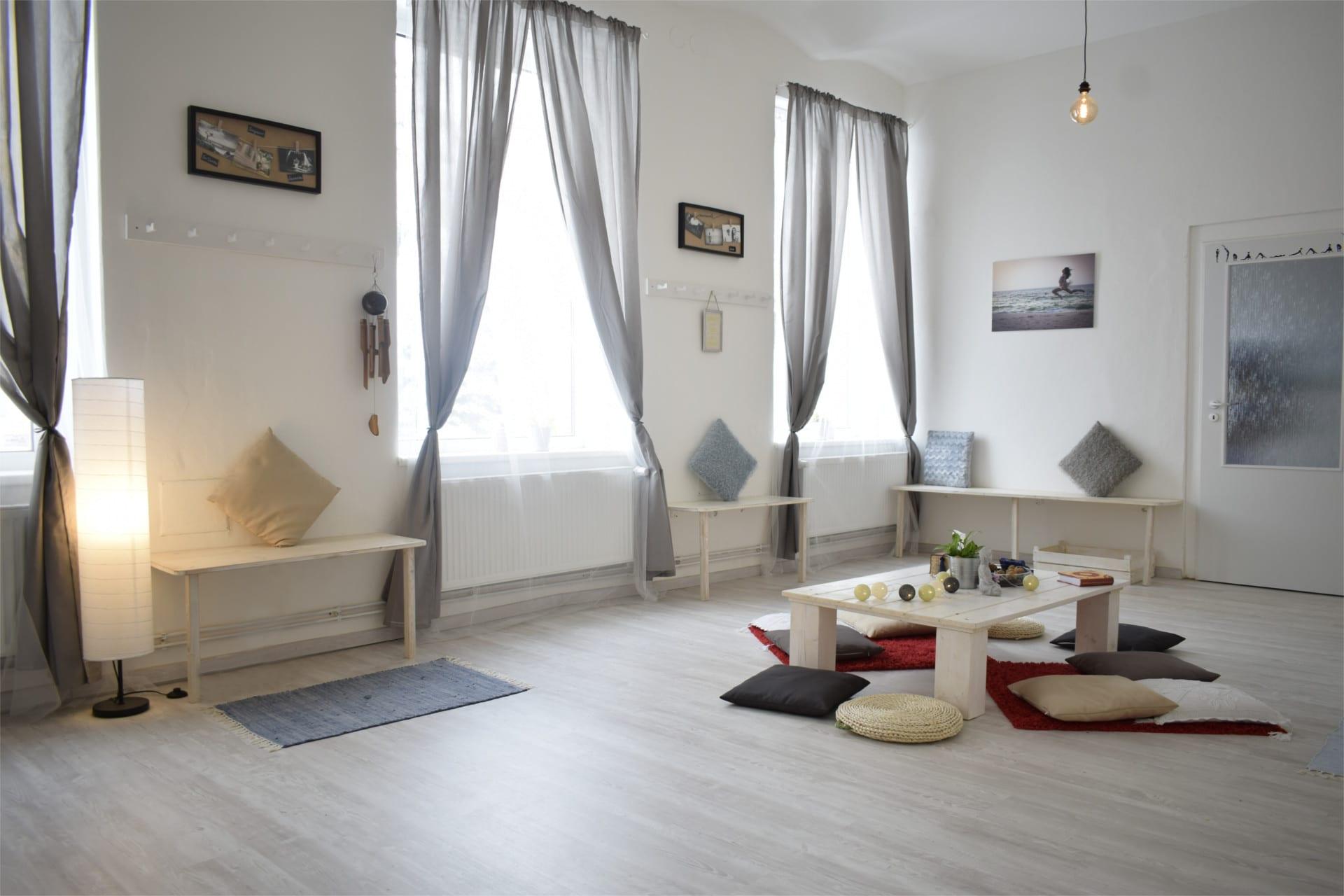 jóga Liberec , šatna v jógovém studiu v Libereci, která je zařízená a leděná do světlých barev, polštáře a dostatek světla to jsou prvky co vévodí této šatně