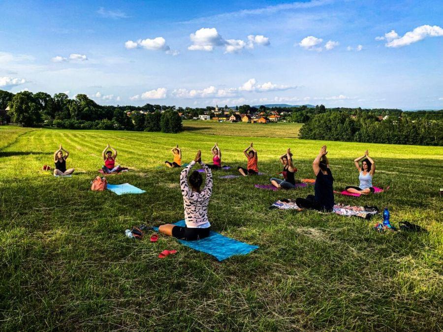 jóga na Sychrově na louce nedaleko místního rybníka, kde je skupina jogínek sedících na podložkách a mají spojené ruce nad hlavou v pozadí je hustý let, jóga Liberec, jóga Turnov