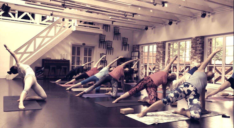 spoustu jogínek ve velkém tanečním sále s černou podlahou a velkými členitými okny v pozadí při jedné z jógových asán, lekce jógy Liberec Turnov