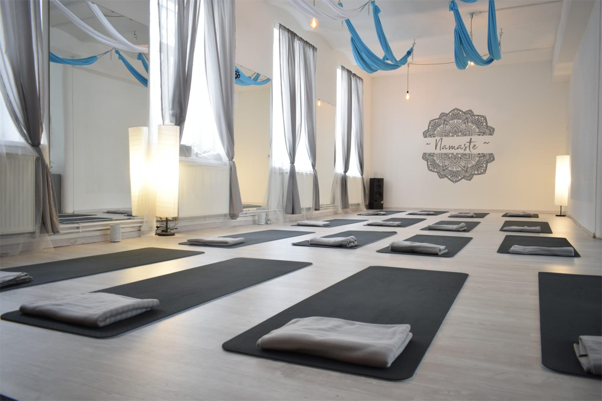 sál jóga Liberec , kde jsou rozmístěny jógové podložky, vzadu je videt velká mandala a sálu dominují zrcadla a dlouhé závěsy, které jsou sladěny tak aby prostor byl naprosto světlý