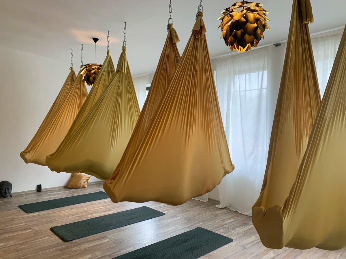 čtyři lidé v Turnovském studiu jógy, kteří ale nejsou vidět, protože jsou kompletně schováni v sítích na letající jógu